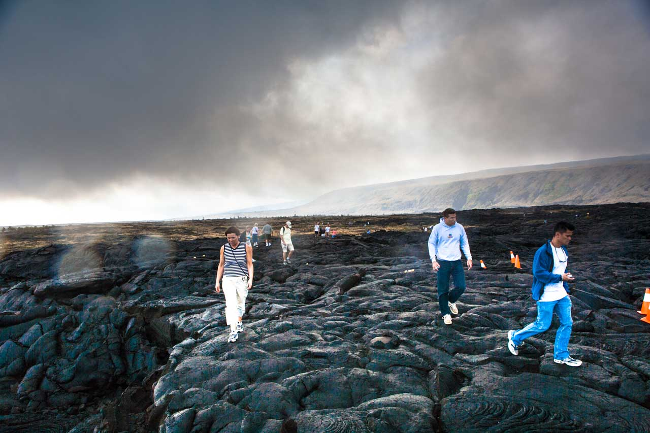 tourists walk on the cooled lava